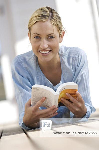 Junge Frau beim Lesen eines Buches  auf der Terrasse liegend