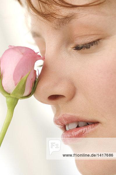 Bildnis der jungen Frau mit Rose vor dem Gesicht  Augen geschlossen