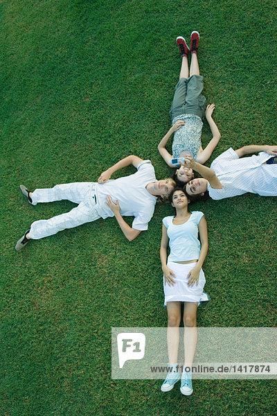 Gruppe junger Freunde auf Gras liegend mit Köpfen zusammen