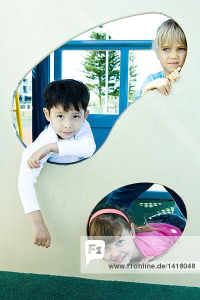 Kinder auf Spielgeräten  lächelnd vor der Kamera