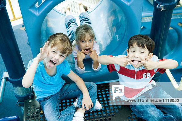 Kinder auf Spielgeräten  Gesichter machen vor der Kamera