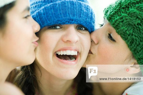 Junge Frau wird von zwei Freunden auf die Wangen geküsst und lächelt in die Kamera.