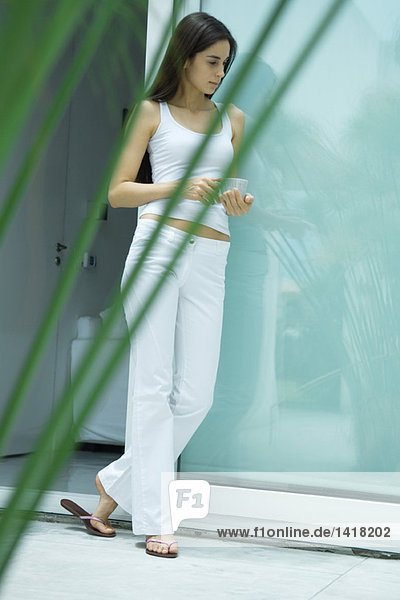 Young woman holding cup and leaning against wall  full length