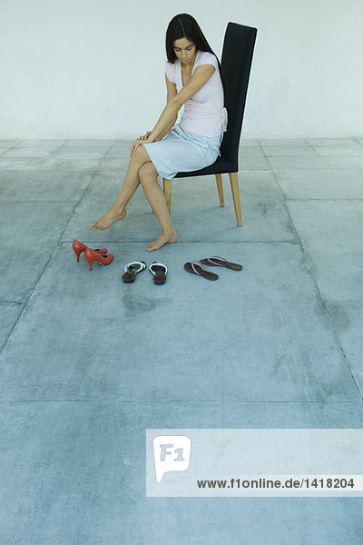 Woman sitting on chair looking at three pairs of shoes  full length