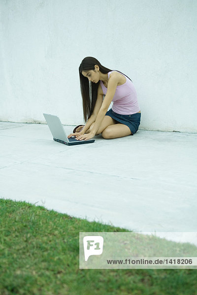 Woman sitting on ground using laptop  full length