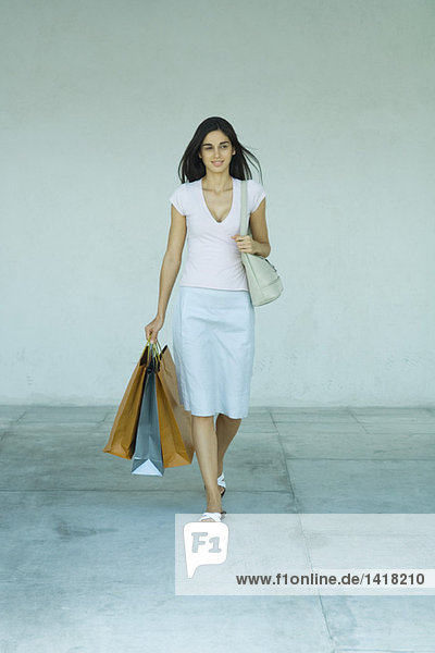 Woman walking with shopping bags  full length