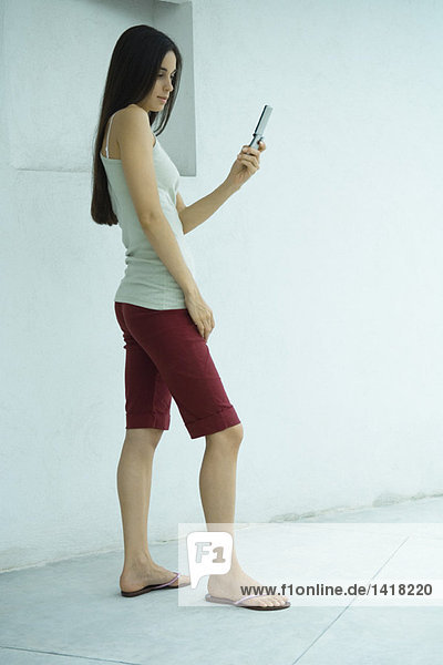 Woman standing  looking at cell phone  full length
