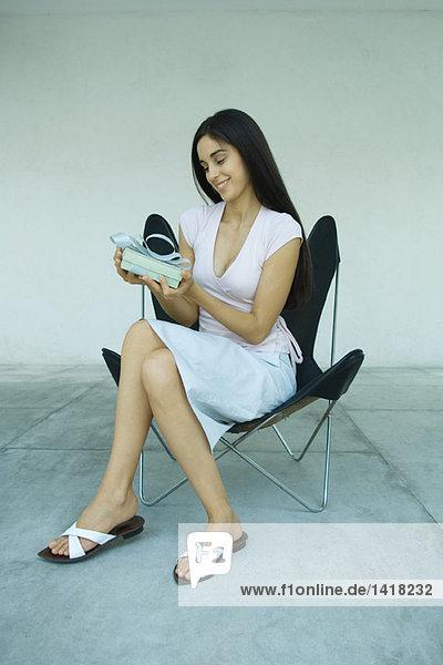Woman sitting  holding gift  full length