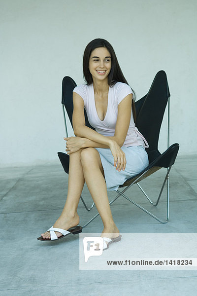 Woman sitting in chair  smiling  full length
