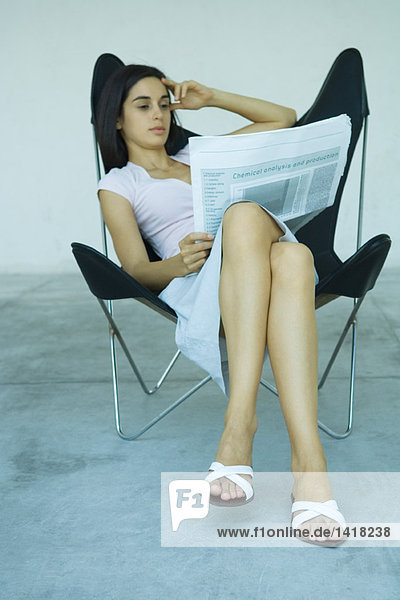Woman sitting in chair  reading newspaper  full length
