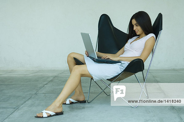 Woman sitting in chair using laptop  full length