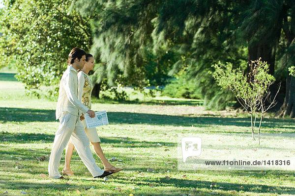 Ein Paar  das gemeinsam über Gras geht.