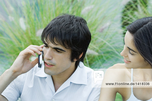 Young man using cell phone while girlfriend waits
