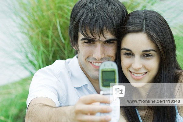 Young couple taking self-portrait with cell phone