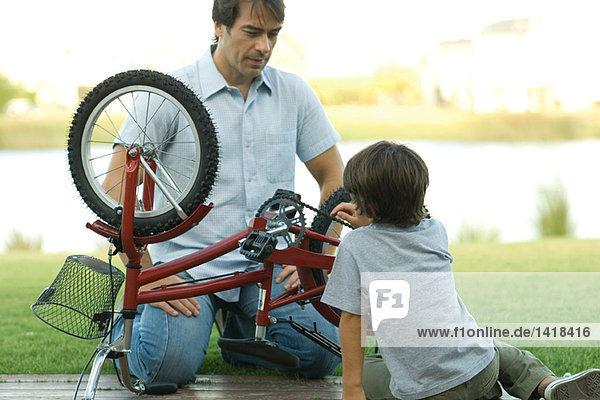 Vater und Sohn reparieren Fahrrad zusammen