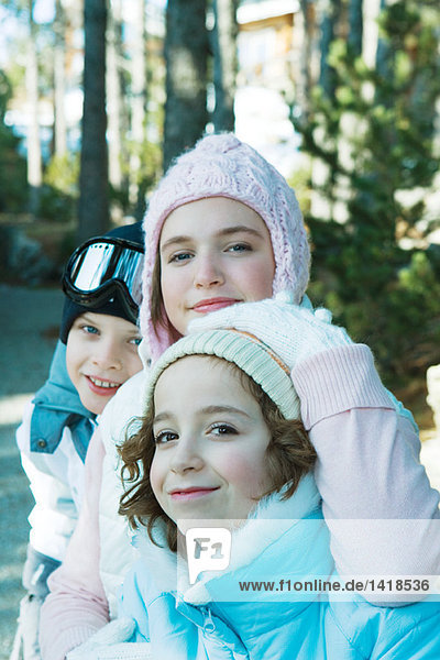 Young friends in ski clothing  looking at camera