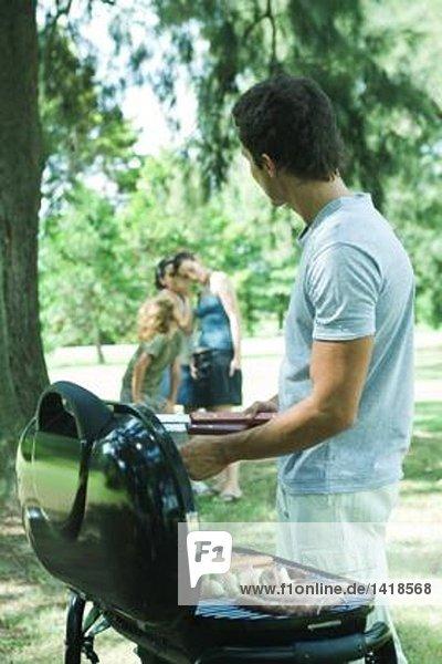 Mann grillt Fleisch auf dem Grill  Familie flüstert im Hintergrund