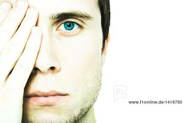 Junger Mann  der ein Auge bedeckt  in die Kamera schaut  extreme Nahaufnahme