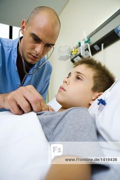 Boy lying in hospital bed  doctor listening to chest with stethoscope