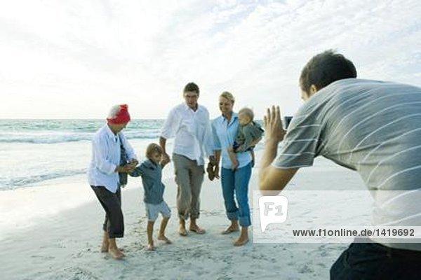Family on beach  man taking photo