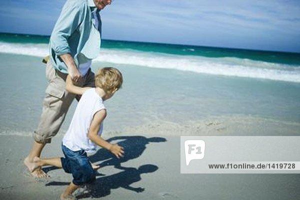 Mann und Junge gehen am Strand spazieren