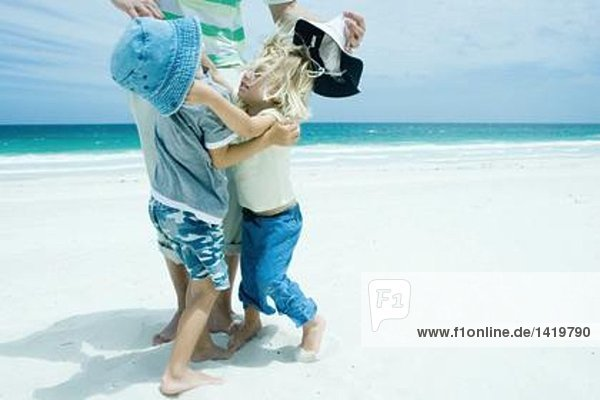 Family on beach  boy and girl reaching for each other in front of father