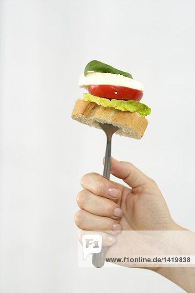 Frau hält eine Gabel mit Baguette,  Salat,  Tomate,  Mozzarella und Basilikum,  fully_released