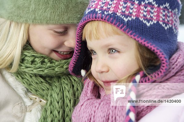 Two girls wearing warm clothing head to head