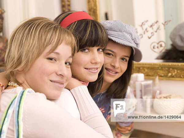 Three girl friends looking to camera  smiling  portrait