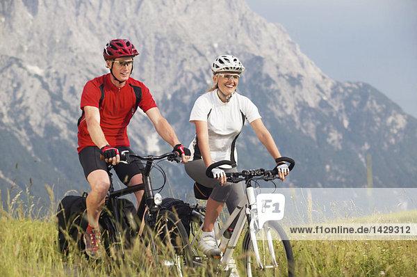 Paar Radfahren über eine Wiese