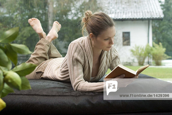 Young woman relaxing on sofa reading a book