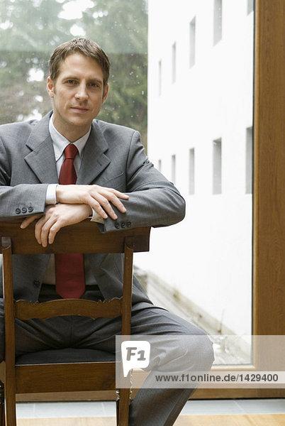 Businessman sitting backwards on a chair