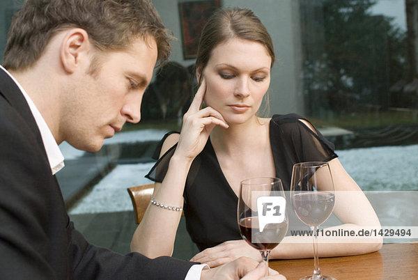 Ein Paar trinkt Rotwein und sieht unglücklich aus.