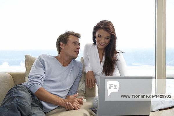 Paar auf der Couch sitzend  mit Laptop