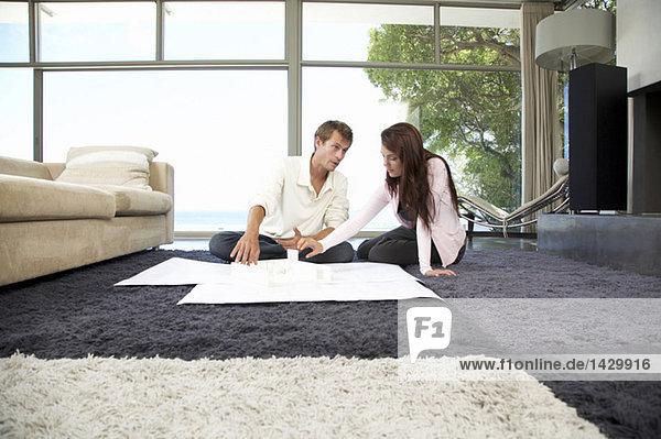Paar im Wohnzimmer mit Bauplänen