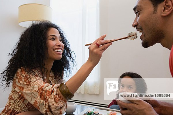Ehefrau füttert Ehemann Sushi