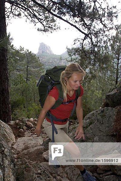 Eine Frau Wandern in Berglandschaft.