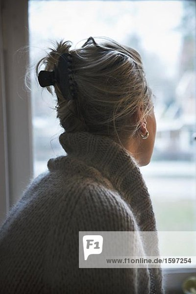 Eine junge Frau Blick aus einem Fenster.