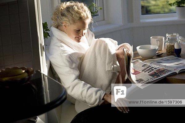 Eine Frau lesen das Papier beim Essen Frühstück.