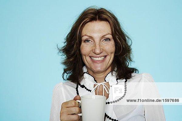 Portrait einer mittleren Alters Frau hält eine Tasse Kaffee.