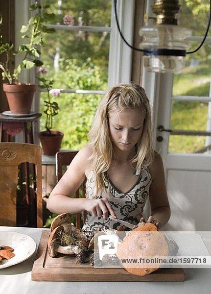 Ein Mädchen Reinigung Pilze. Ein Mädchen Reinigung Pilze.