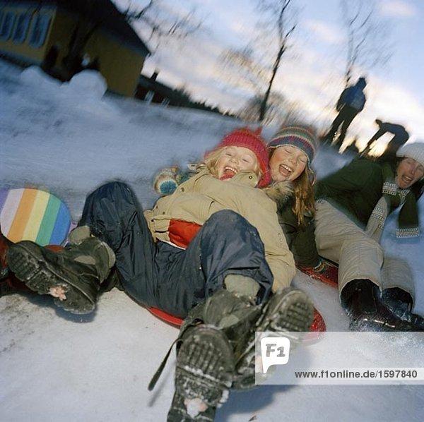 Zwei Kinder auf ein Kunststoff Schlitten ein Frau Recht hinter ihnen Nyckelviken Nacka Schweden.