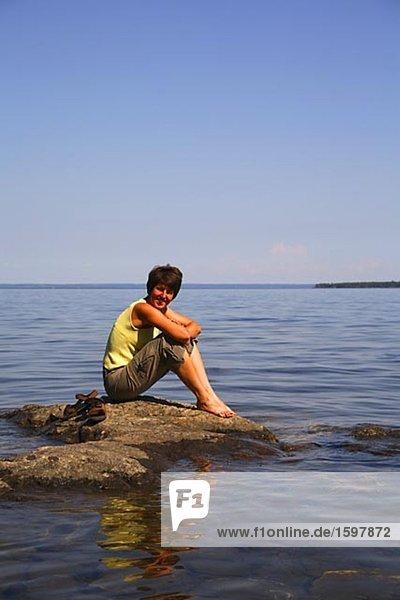 Woman sitting on a rock Storsjon Jamtland Sweden.