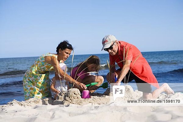 Two adults and two children building a sand castle Oland Sweden.