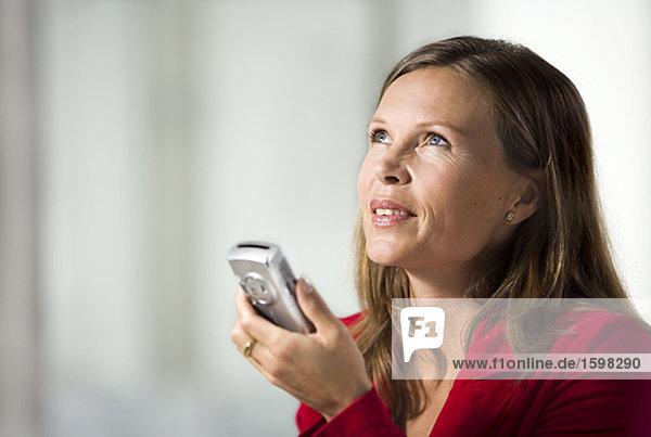 Eine Frau mit einem Handy in einem Büro.