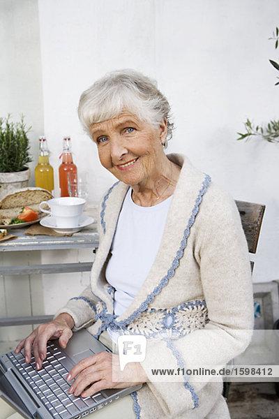 Eine ältere Frau Schreiben auf ihrem Computer Schweden.