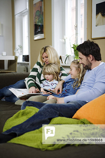 Eine Familie in einer Lesung Sofa sitzen.