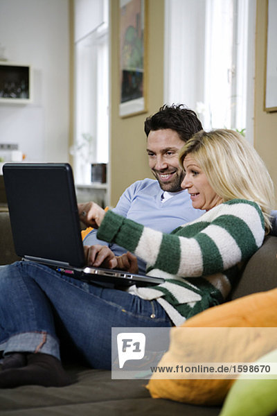 Ein paar mit einem Computer in einem Sofa.