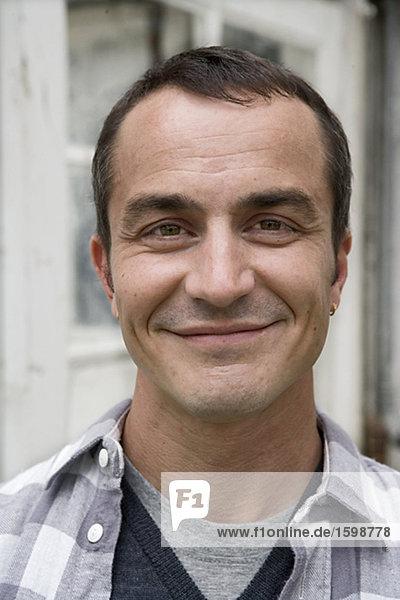 Porträt von einem lächelnd Mann mittleren Alters.