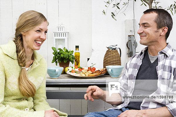 Ein im mittleren Alter Paar mit Kaffee in einem Gewächshaus.